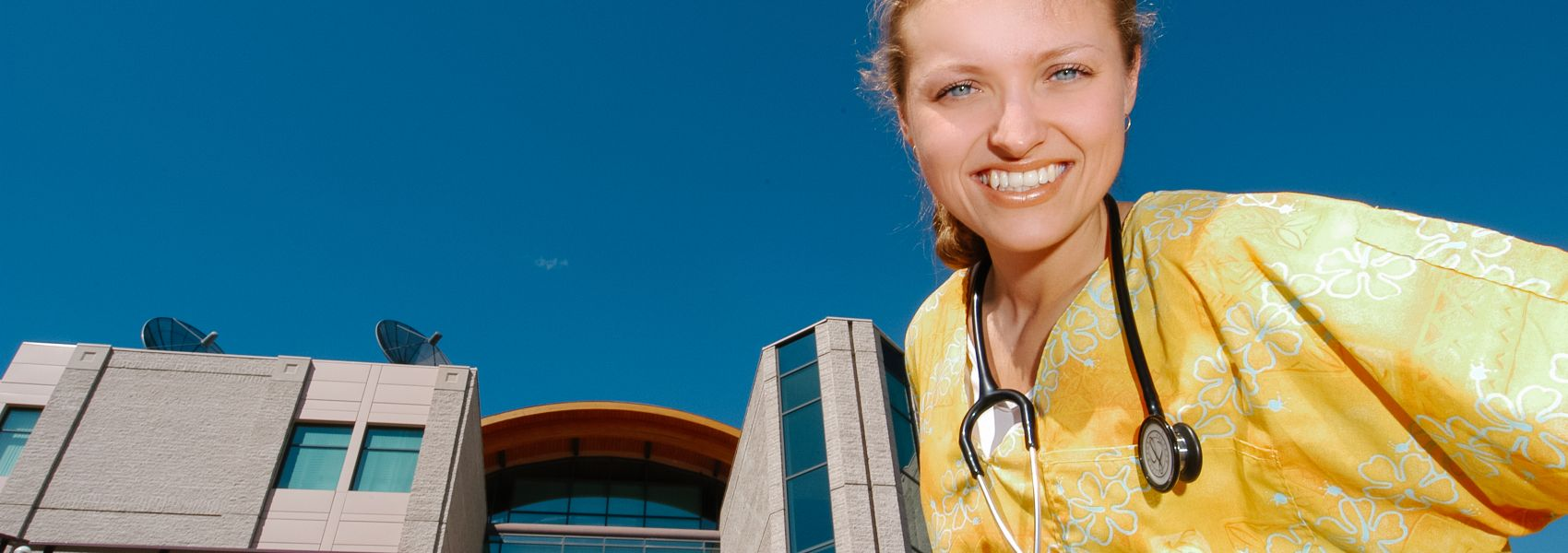 Nursing student standing in front of a UNBC building